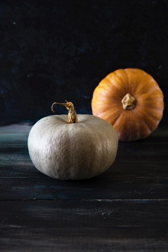 Two pumpkins on a wooden background