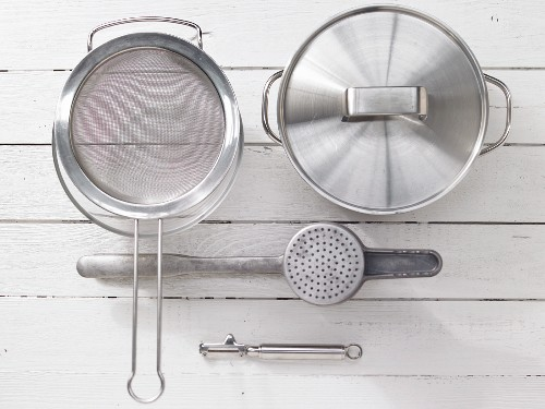 Various kitchen utensils: sieve, cooking pot, potato press, vegetable peeler