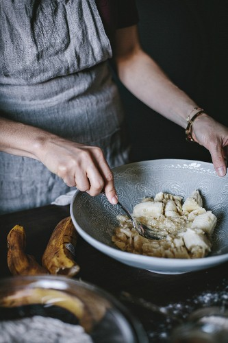 A woman is mashing bananas to be used in a banana bread donut recipe