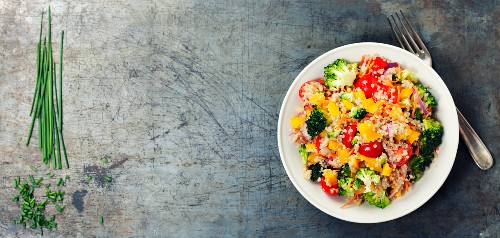 Quinoa salad with broccoli, bell peppers, carrot, onion and tomatoes on a rustic metal background