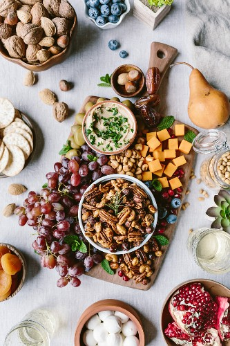 A bowl of spicy candied pecans, cheese and fruit board