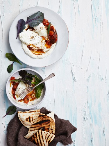 Poached eggs on harissa with stewed tomatoes and grilled flatbread