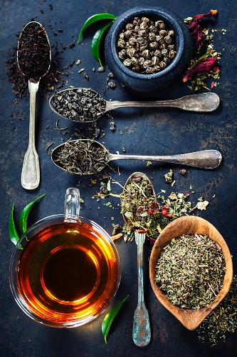 Tea composition with Different kind of tea and old spoons on dark background