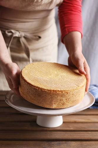 Biskuitkuchen wird auf Kuchenständer platziert