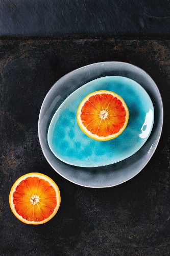 Sliced Sicilian Blood orange fruit on bright turquoise and gray ceramic plates over black background
