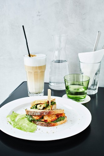 Close-up of chicken and spinach sandwich with cafe latte on restaurant table
