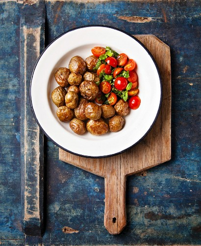 Young baked potatoes with tomato on white plate
