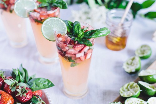 A glass of Honey Sweetened Limeade with Strawberries and Basil