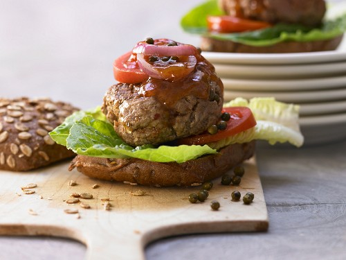 A burger with onions, chilli paste and mango chutney