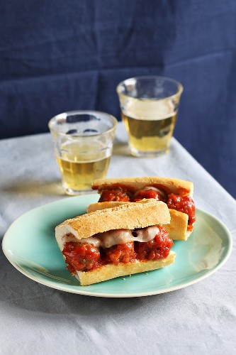 Two meatball sandwiches on a plate with two glasses of fresh beer