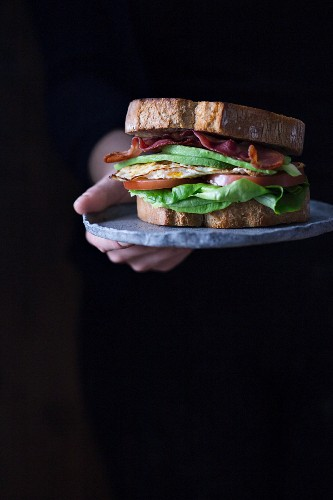 Sandwich with fried egg, bacon, avokado, tomatoes and lettuce