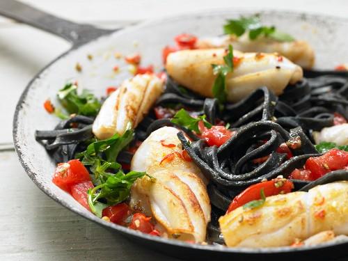 Schwarze Pasta mit Tintenfisch und Tomaten