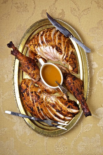 Presentation of sliced turkey with gravy in a gravy boat on a metal plateDark and white meat