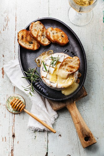 Baked Camembert cheese with toasted bread on cast-iron frying pan