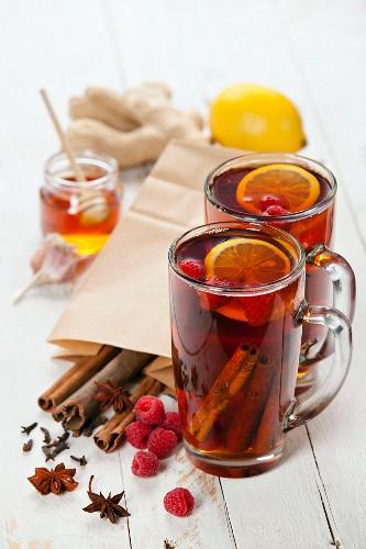 Cup of Hot winter raspberry tea with cinnamon sticks, lemon and star anise