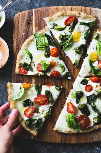 Padron pepper and cherry tomato pizza, gluten-free and whole-grain, a hand taking a slice