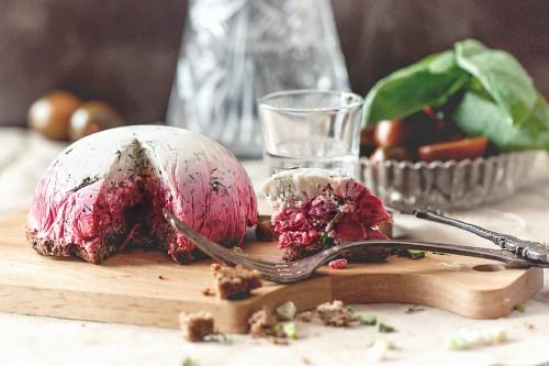 Pastete mit Heringssalat auf Holzbrett mit Gabel und russischer Wodka