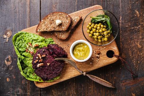 Beet cutlet vegan meatless served with green peas salad on dark wooden background