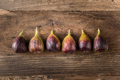 Row of fresh figs on a wooden table