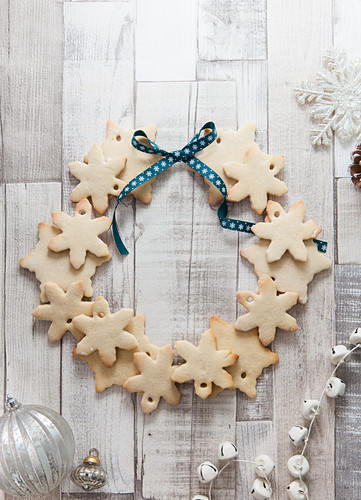Snowflake shaped biscuits arranged to make a Christmas wreath on a rustic white wood surface