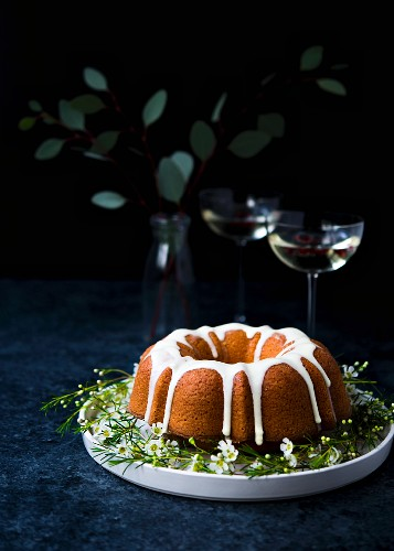 Olive oil and orange ring cake on a plate with champagne glasses in the background