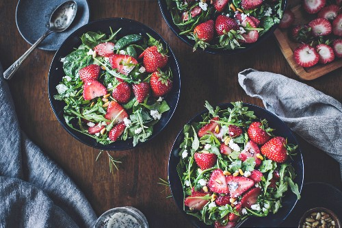 Three bowls of strawberry, spinach and arugula salad
