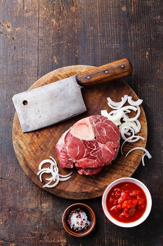 Raw fresh cross cut veal shank and Ingredients for making Osso Buco on wooden cutting board on dark wooden background