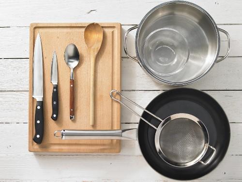 Various kitchen utensils: pot, pan, sieve, knives, spoon