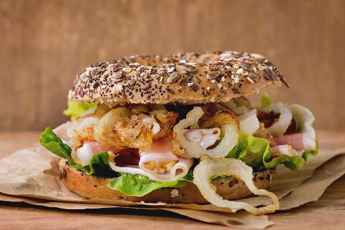 Whole Grain bagel with fried onion, green salad and prosciutto ham on paper