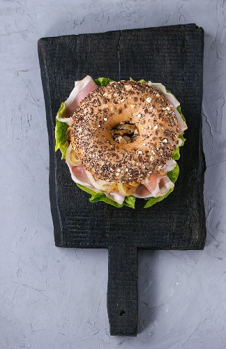 Whole Grain bagel with fried onion, green salad and prosciutto ham on black wood choping board