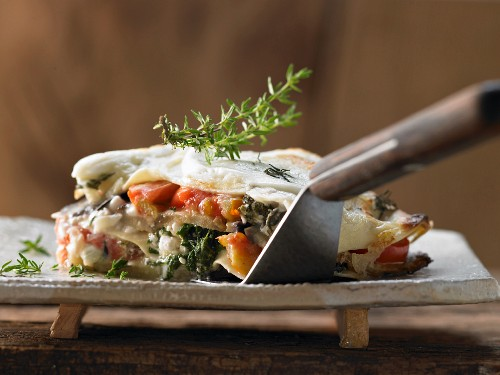 Aubergine lasagne with baby leaf spinach and tomatoes