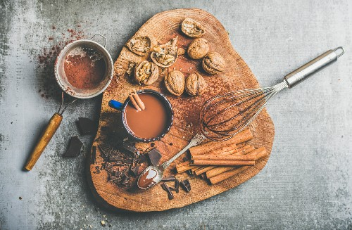 Rich winter hot chocolate with cinnamon sticks and walnuts in blue enamel mug on wooden board