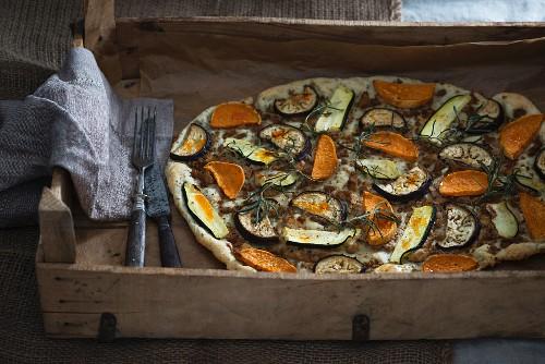 Vegan tarte flambée with sweet potato, zucchini, aubergine, tofu and rosemary