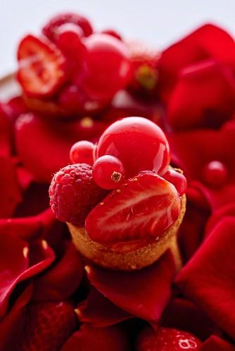 Mini-Tartelett mit roten Früchten auf Rosenblütenblättern
