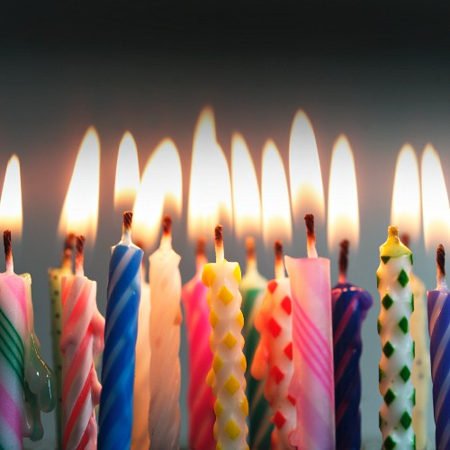 Colourful lit birthday-cake candles (close-up)