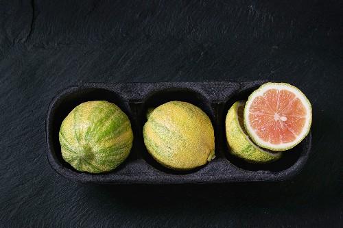 whole and sliced citrus fruit pink tiger lemon in paper market box over black stone slate textured background