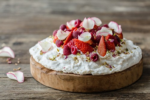 Rose and pistachio pavlova with fresh strawberries and raspberries, decorated with pistachio nuts and dried and fresh rose petals on a wooden surface