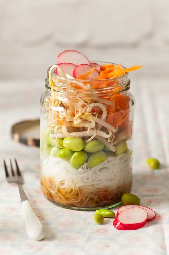 Japanese oriental edamame bean raw lunch jar with fork and lid on the cloth surface