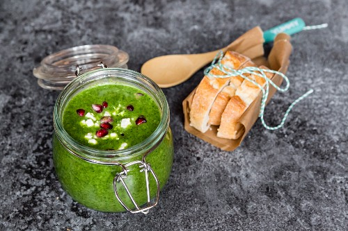 Green cabbage soup in a glass jar with pomegranate seeds and feta cubes