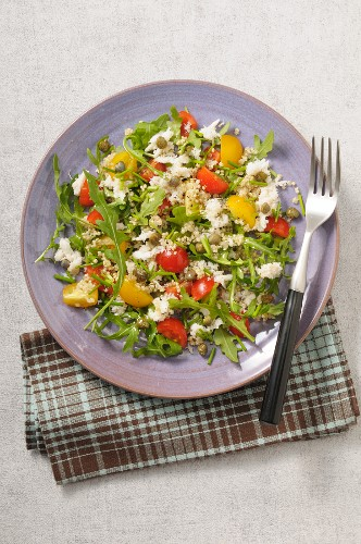 Quinoa salad with crab meat, tomatoes and arugula