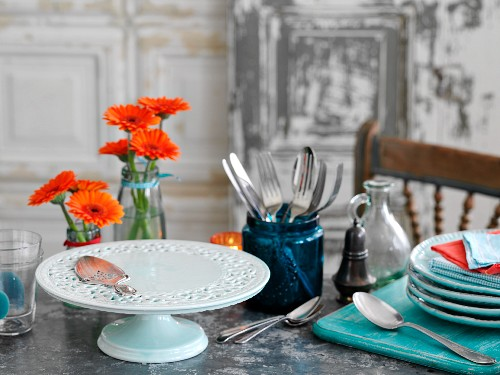 Plates, cutlery, flowers and a cake stand for a buffet