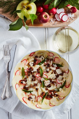 An apple and radish salad with herbs, hazelnuts and mint