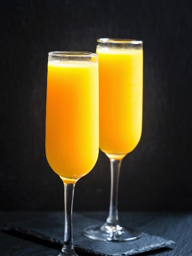 Two glasses of freshly squeezed orange juice in front of a black background