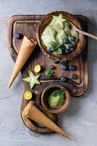 Bowl of Green tea matcha soft elastic ice cream with mint leaves, carambola, lime, blueberries and waffle cones