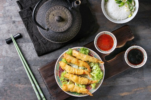 Fried tempura shrimps on lettuce salad with sauces