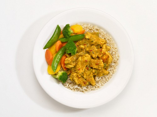 Chicken masala with vegetables and rice on a plate in front of a white background