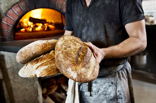 A baker holding several freshly baked wood oven bread loaves in his hands