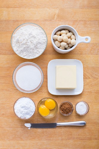 Ingredients for making macadamia and cinnamon biscuits with icing sugar