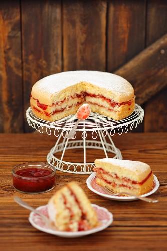 Victoria sponge cake with strawberry jam on a cake rack