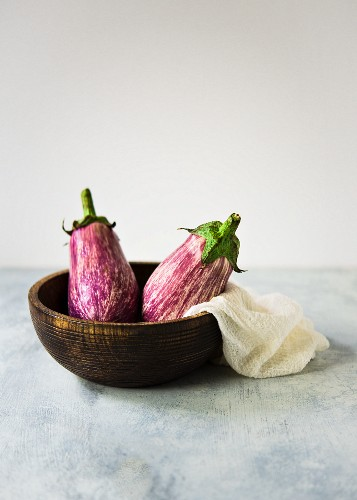 Two striped graffiti aubergines in a wooden bowl